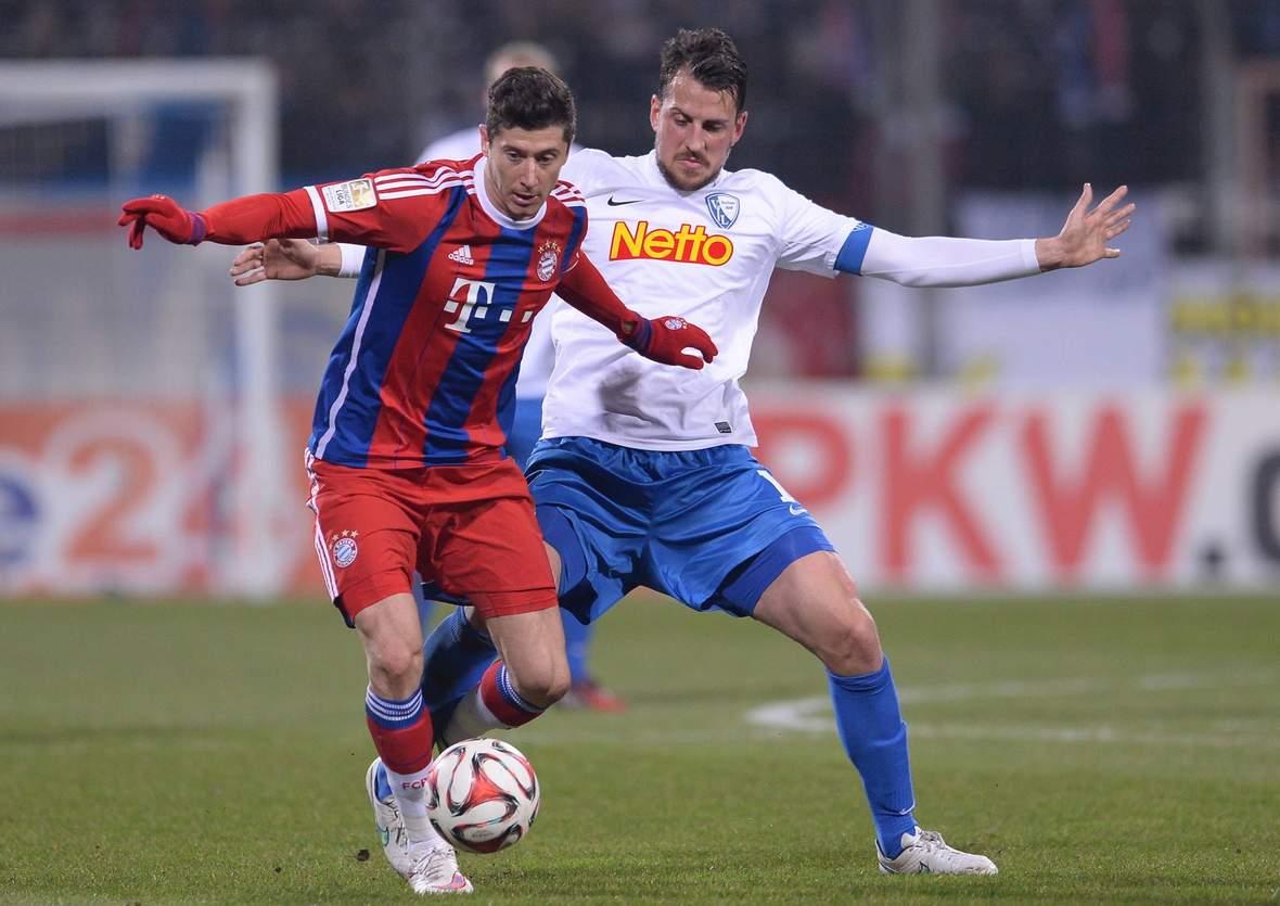 Robert Lewandowski im Zweikampf mit Patrick Fabian. Unser Tipp: Bayern gewinnt in Bochum.